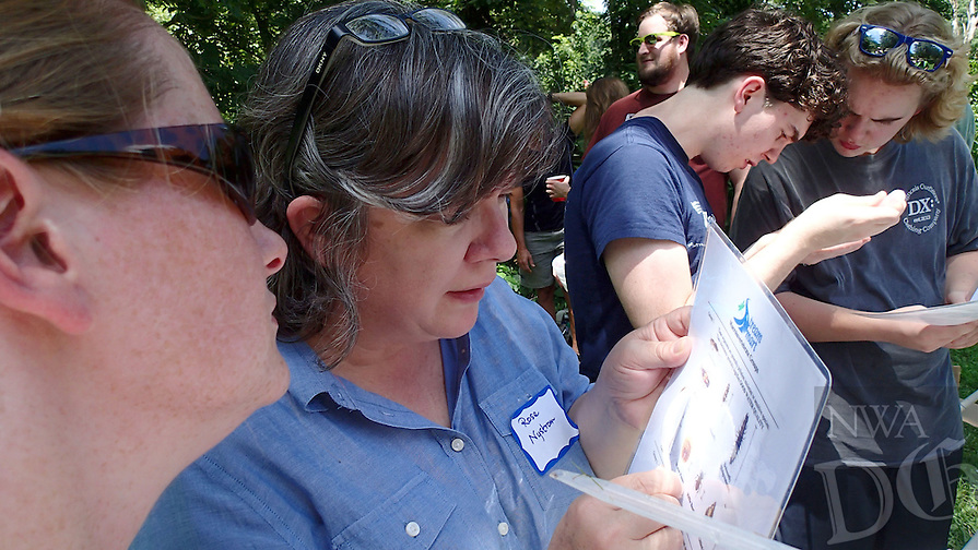NWA Democrat-Gazette/FLIP PUTTHOFF <br /> Rose Nystrom (second from left) uses a study sheet       July 2016      to identify aquatic insects.