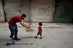 Nour, a 18-year-old Syrian man, plays wit his relative boy in a rebel-controlled area of Aleppo, on August 13, 2015. Nour lost his leg following a bomb barrel attack by forces of Syria's President Bashar al-Assad near his house in Bustan al-Qasr district. A report from the Syrian Observatory for Human Rights (SOHR) claims that over 1,000 children have been killed in airstrikes during the nation's ongoing civil war, an additional 1.5 million people have been wounded for life in the airstrikes that have been carried out by Syria's government since the Syrian conflict. Photo by Ameer al-Halbi