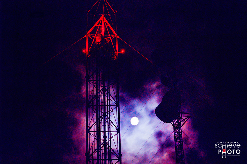 Moon behind television towers.