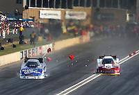 Jul. 19, 2014; Morrison, CO, USA; NHRA funny car driver Tim Wilkerson (right) crosses the centerline hitting the timing blocks alongside Tommy Johnson Jr during qualifying for the Mile High Nationals at Bandimere Speedway. Mandatory Credit: Mark J. Rebilas-