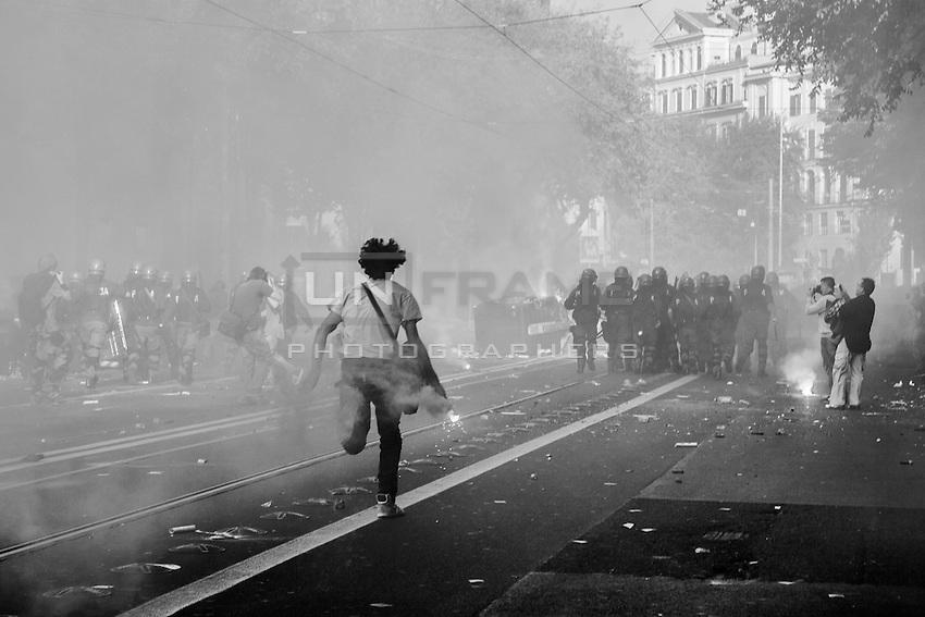 A rioter runs towards a police blockade holding a candle smoke. Rome, Italy. 15/10/2011