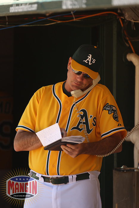 OAKLAND, CA - JUNE 16:  Pitching coach Ron Romanick #37 of the Oakland Athletics talks on the bullpen phone during the game against the Kansas City Royals at the Oakland-Alameda County Coliseum on Thursday, June 16, 2011 in Oakland, California. Photo by Brad Mangin