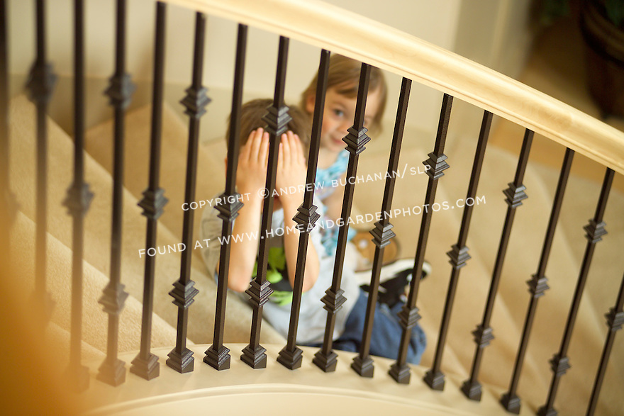 a four year old girl sits slightly behind a five year old boy on a curving staircase as seen through the banister railing from upstairs and behind them, while the boy plays a game of peek with his hands