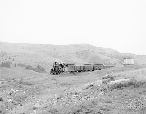 D&amp;RGW #476 with eastbound San Juan passing Los Pinos water tank.  A freight can be seen on lower level waiting for the meet.<br /> D&amp;RGW  Los Pinos, CO  Taken by Richardson, Robert W. - 7/22/1949