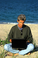 Man working on a laptop computer while at the beach.