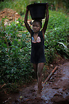 A girl carries water over head. In many developing countries children seen in the need to work to have access to the most basic things, help their families, go to school, food or water are just some of them.