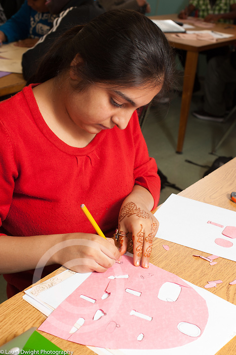 Education High School elective female student with henna (mehndi) on hand working on art activity