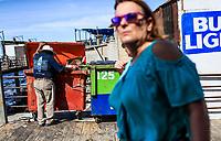 Puerto Peñasco, Sonora, October 20, 2017.-<br /> Two American women tourists stroll the tourist dock of Puerto Peñasco while a May adult man of extreme poverty looks for food inside the trash contents.<br /> Dos mujeres turistas norteamericanas pasean por el muelle turístico de Puerto Peñasco mientras un hombre adulto mayo de pobreza extrema  busca comida dentro de los contenidos de basura.<br /> (Foto: Luis Gutierrez /NortePhoto.com)
