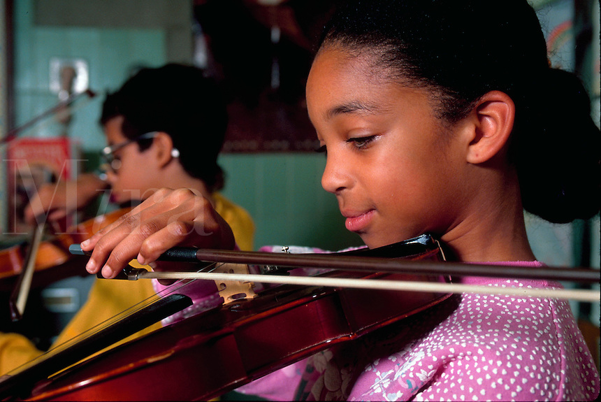 A smiling young African American female student practices playing the violin.