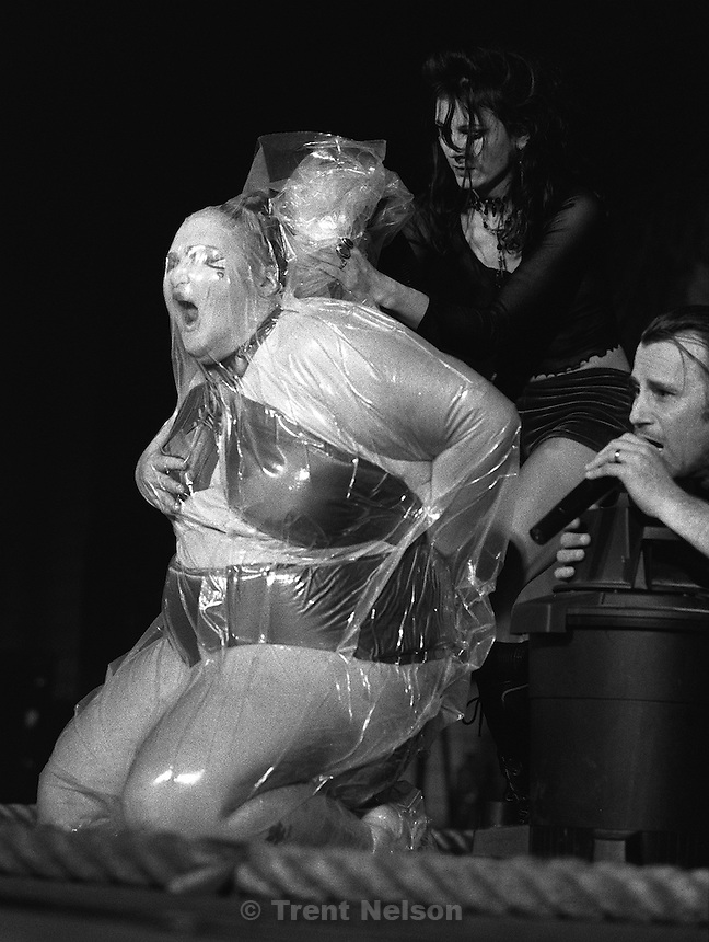 Woman in plastic bag with vacuum sucking the air out during the Jim Rose Circus at Brick's.