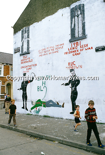 CHILDREN PLAYING ON THE STREET BESIDE ANTI 'H' BLOCK WALL PAINTING IN BELFAST,