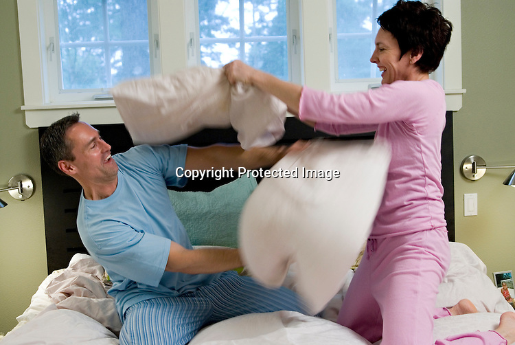 Mature couple having a light hearted pillow fight in bed