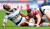 PICTURE BY VAUGHN RIDLEY/SWPIX.COM - Rugby League - Super League - Huddersfield Giants v Hull FC - Galpharm Stadium, Huddersfield, England - 09/04/12 - Hull FC's Willie Manu cries out in pain after his leg is caught underneath Huddersfield's Danny Brough.