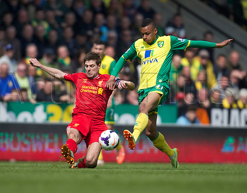 20.04.2014.  Norwich, England.  Steven Gerrard of Liverpool (left) makes the challenge on Joshua Murphy of Norwich City during the Barclays Premier League match between Norwich City and Liverpool from Carrow Road.