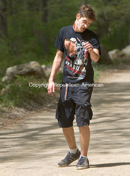 WASHINGTON CT. 09 May 2015-050915SV013-Ray Cook, 17, of Washington dressed as Zobbie drags his leg dou=wn a dirt road looking for runners during the 5K Zombie Run Against Epilepsy at the Steep Rock Preserve in Washington Depot Saturday.<br /> Steven Valenti Republican-American