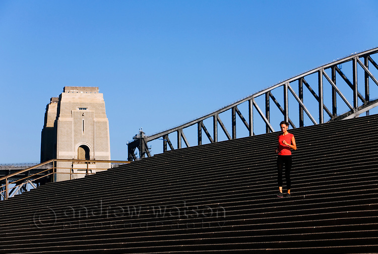 A woman runs across the steps of the Sydney Opera House.  Sydney, New South Wales, AUSTRALIA.