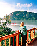USA, Alaska, woman watches a float plane take off at Redoubt Bay, Redoubt Bay Lodge