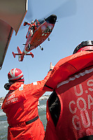 A United States Coast Guard HH-65C Dolphin helicopter works with the crew of a Coast Guard Auxiliary vessel. The helicopter and crew, based at U.S. Coast Guard Air Station San Francisco, was on a practice mission with the Coast Guard Auxilary to maintain search and rescue proficiency.