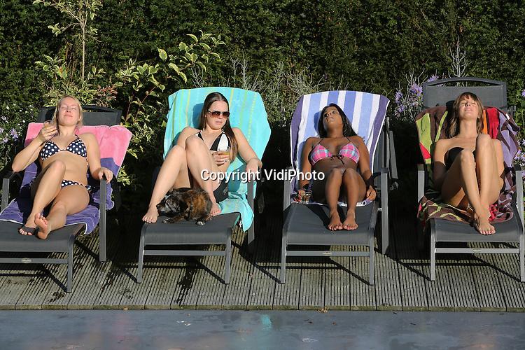 Foto: VidiPhoto<br /> <br /> LEERSUM - Zomers tafereel. Genieten in en bij het buitenzwembad van de familie De Jong in Leersum dinsdag. Op diverse plaatsen steeg de temperatuur naar de 23 graden en dan is het warm genoeg om te zonnebaden. Zo ook de vriendinnen van Marieke de Jong (tweede van links) die herfstvakantie kwam vieren bij het priv&eacute;zwembad van de Leersumse familie. Nog niet eerder deden ze dat op deze zomerse wijze.