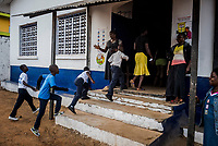 """MONROVIA, LIBERIA - FEBRUARY 17: Vice principal, Venoria Crayton, watches as students head to class on the second day of school, since schools closed due to the Ebola outbreak 6 months ago, at the C.D.B. King Elementary School on February 17, 2015 in Monrovia, Liberia. Ebola destroyed and devastated our land,'' Venoria Crayton, the vice principal, told her pupils. """"It brought us sadness, it brought us pain. Some of your neighbors died, right? Some of your neighbor's children died, right? But you are here."""" Though Ebola cases have receded into the single digits in Liberia, lingering fear and a depressed economy have dampened the turnout at schools. Many have yet to reopen, having failed to meet the minimum requirements put in place to prevent the transmission of the virus. Many of those that have reopened – like C.D.B. King, which, though located in the center of the capital, lacks electricity and running water, and has only a few toilet stalls for a student population that numbered 1,000 before Ebola — are struggling.<br /> Daniel Berehulak for The New York Times"""