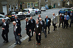 Askrigg Equitable Benevolent and Friendly Society. Askrigg north Yorkshire UK. The annual walk back from church behind the Friendly Society banner Honorary members wear white rosettes while ordinary members wear blue