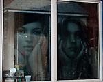 Beauty product posters reflect in a window.  Key West, Florida, USA.