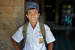 Jefrin Zendrato, 13, poses in his school uniform in his village of Moawo on the Indonesian island of Nias. As a small child, he helped plant mangrove seedlings along the nearby coastline following a devastating 2004 tsunami and 2005 earthquake. The mangrove planting was part of assistance provided to the village by YEU, a member of the ACT Alliance. His family's house was flattened by the waves, and after months of living in temporary shelters on nearby hillsides, he and his family moved into one of 72 new homes constructed in the village by YEU. With foundations of cement, they are more resilient than the pre-tsunami houses which were built entirely of wood. YEU also helped the community members restart their local economy, including the replanting of mangroves to protect the shoreline and revitalize their fishing industry. <br /> <br /> (Parental consent obtained.)