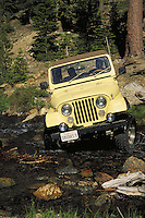 four wheel drive vehicle crossing stream bed with rocks at Dobkins Lake area. California.