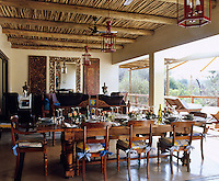 In old-fashioned colonial style, a dining room is situated under the cane ceiling of the outdoor terrace of a country house hotel in Africa