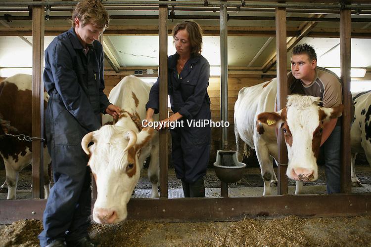 Foto: VidiPhoto..RHENEN - Vakantiebaantje Corine Bruggink samen met Gerard de Jong (l) op de boerderij van Gert van Laar uit Rhenen.