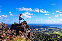 A hiker takes in the awesome sunrise view from the chin of the Sleeping Giant (or Nounou Mountain), eastern Kaua'i.