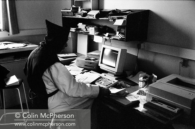 A monk working on a computer in the office at Sancta Maria Abbey at Nunraw, East Lothian, home since 1946 to the Order of Cistercians of the Strict Observance. Around 15 monks were resident at Nunraw in 1996, undertaking a mixture of daily tasks and strict religious observance. The present purpose-built building dates from 1969 when the monks moved from the nearby Nunraw house.