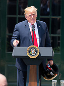 United States President Donald J. Trump holds the racing helmet he received as a gift as he hosts Martin Truex Jr., the NASCAR Cup Series champion, and his team, on the South Lawn of the White House in Washington, DC on Monday, May 21, 2018.  Truex competes full-time in the Monster Energy NASCAR Cup Series for Furniture Row Racing.<br /> Credit: Ron Sachs / CNP