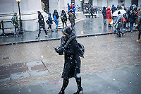 A woman braves the cold and snow in front of the New York Stock Exchange while dutifully checking her smartphone on Tuesday, January 31, 2017. The snow will wind down by the late afternoon leaving only about an inch in the city. (© Richard B. Levine)