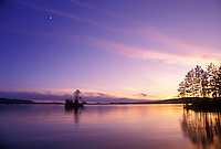 Moosehead Lake, Lake Region, Maine, (Sunset, sunrise) over the calm Moosehead Lake shows the refection of trees in the water.