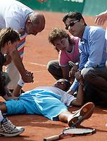 13-8-06,Den Haag, Tennis Nationale Jeugdkampioenschappen, Xander Spong ligt geveld door kramp op het gravel na zijn overwinning bij de 16 jarige en wordt ondersteund door zijn vader