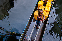 A Colombian boy stands in a canoe, filled by barrels of safe drinking water, inside the stilt house area in Tumaco, Colombia, 17 June 2010. Although Latin America (as a whole) is blessed with an abundance of fresh water, having 20% of global water resources in the the Amazon Basin and the highest annual rainfall of any region in the world, an estimated 50-70 million Latin Americans (one-tenth of the continent's population) lack access to safe water and 100 million people have no access to any safe sanitation. Complicated geographical conditions (mainly on the Pacific coast), unregulated industrialization (causing environmental pollution) and massive urban poverty, combined with deep social inequality, have caused a severe water supply shortage in many Latin American regions.
