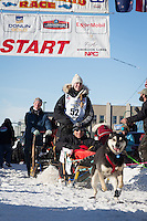 Anna Berington and team leave the ceremonial start line at 4th Avenue and D street in downtown Anchorage during the 2014 Iditarod race.<br /> Photo by Jim R. Kohl/IditarodPhotos.com