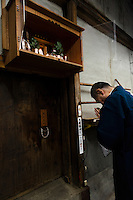 "Tokubee Masuda, CEO of the Tsukinokatsura sake brewery attending to the brewery's shinto shrine. Fushimi, Kyoto, Japan, October 10, 2015. Tsukinokatsura Sake Brewery was founded in 1675 and has been run by 14 generations of the Masuda family. Based in the famous sake brewing region of Fushimi, Kyoto, it has a claim to be the first sake brewery ever to produce ""nigori"" cloudy sake. It also brews and sells the oldest ""koshu"" matured sake in Japan."