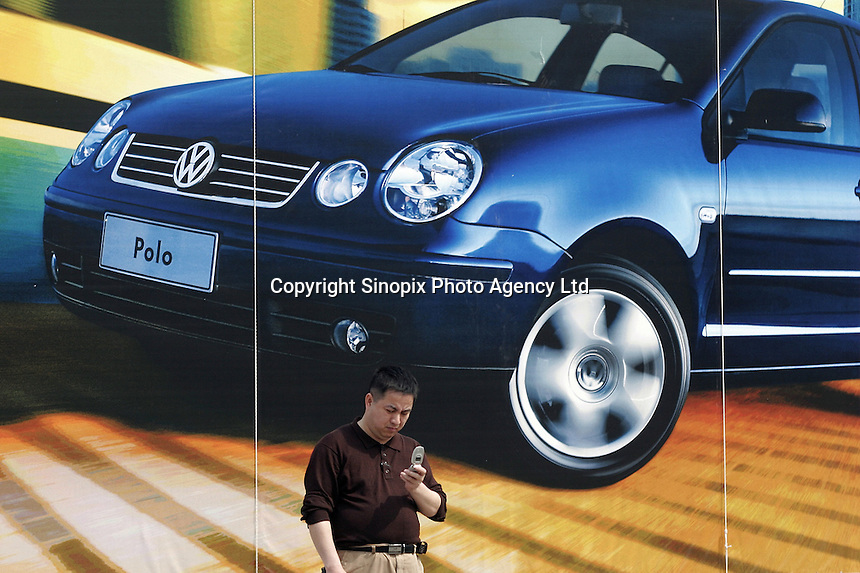 A man stands under an advertisement for Volkswagen in Shanghai, China..