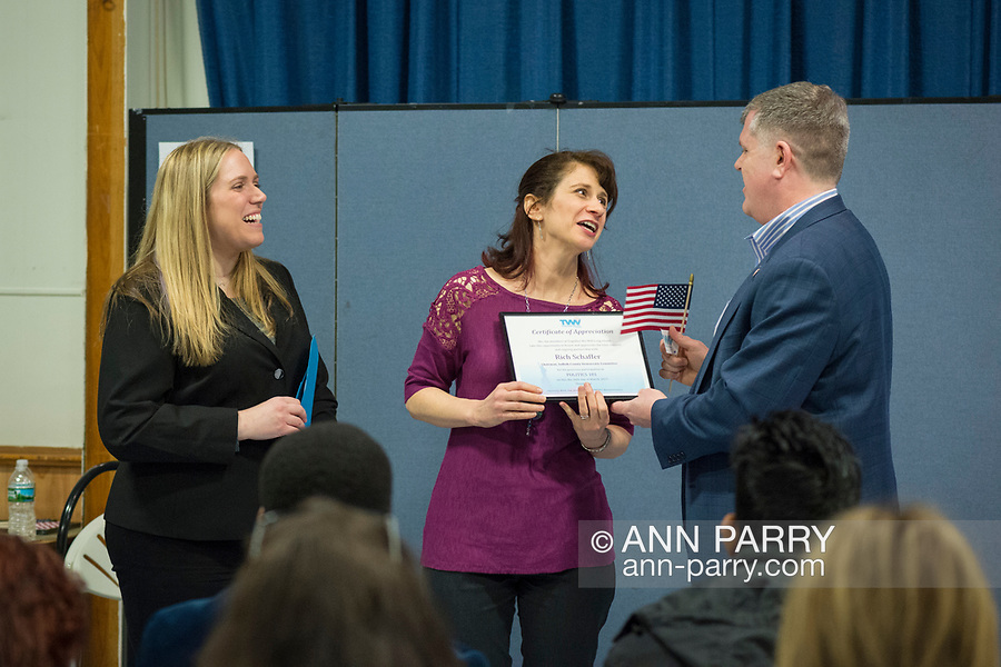 Wyandanch, New York, USA. March 26, 2017. At right, RICH SCHAFFER, Chairman of Suffolk County Democratic Committee, accepts Certificate of Appreciation and American Flag presented by, (center) BETH MEHRTENS McMANUS, and (left) SUE MOLLER, two administrators of Together We Will Long Island. Schaffer spoke at Politics 101 event, the first of a series of activist training workshops for members of TWW LI, the L.I. affilitate of TWW.