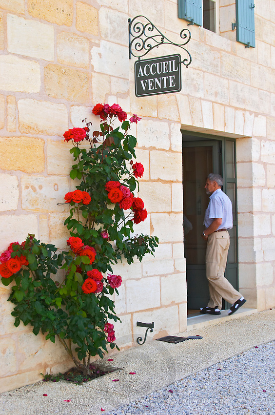 The visitors' reception room with a rose bush with gigantic flowers and a sign saying 'accueil vente' (reception, sales) and a person walking in through the door Chateau Thieuley La Sauve Majeure Entre-deux-Mers Bordeaux Gironde Aquitaine France