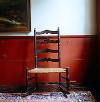 An elegant antique ladder-back chair is placed against warm red-painted panelling in the dining room