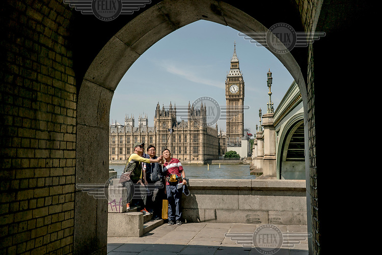 Tourists photograph themselves in front of the Houses of Parliament.