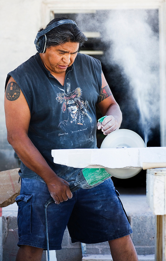 Artist Cliff Fragua uses a grinder with a diamond blade to cut into a piece of marble for a sculpture he's creating at Singing Stone Studio in Jemez Pueblo.