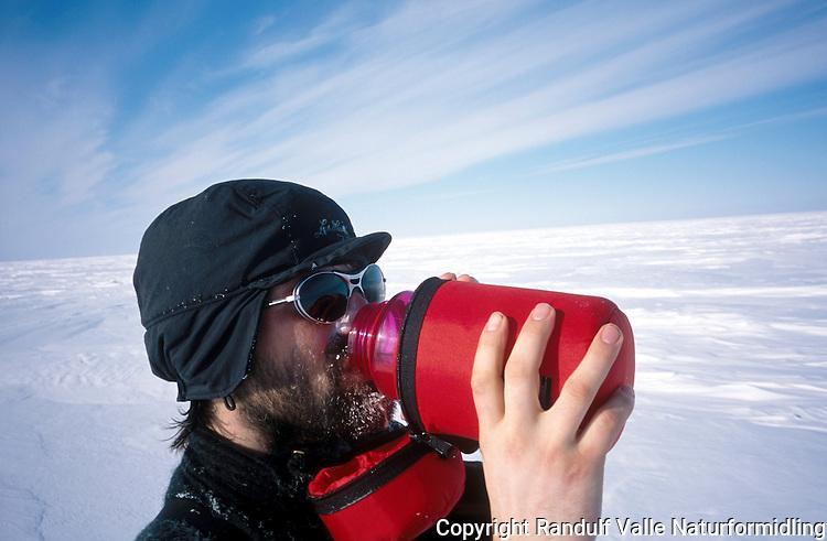 Mann drikker fra isolert drikkeflaske. ---- Man drinking from insulated bottle.