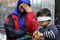 Pictured: A mother puts her hand on her forehead in despair as her young son, who seems to be injured in the head eats snacks in Victoria Square, Athens Monday 29 February 2016<br /> Re: Hundreds of migrants have been living in Victoria Square in central Athens Greece