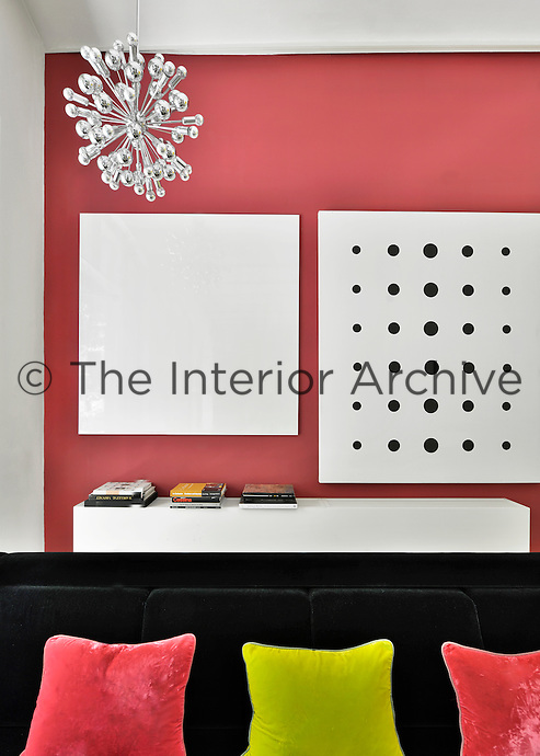 A contemporary white living room with vibrant accent colours. A black sofa provides a strong colour contrast against a coral pink wall upon which is hung white and black canvases.
