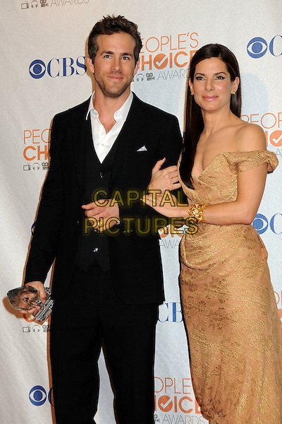 RYAN REYNOLDS & SANDRA BULLOCK.Pressroom at the 36th Annual People's Choice Awards held at the Nokia Theatre LA Live, Los Angeles, California, USA..January 6th, 2009.press room half length dress award trophy winner beige gold earrings one off the shoulder strap bare off the black suit 3/4.CAP/ADM/BP.©Byron Purvis/AdMedia/Capital Pictures.