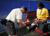 Black (Afro-American) woman college soccer player having her ankle injury tended to by male sports trainer, California. California.